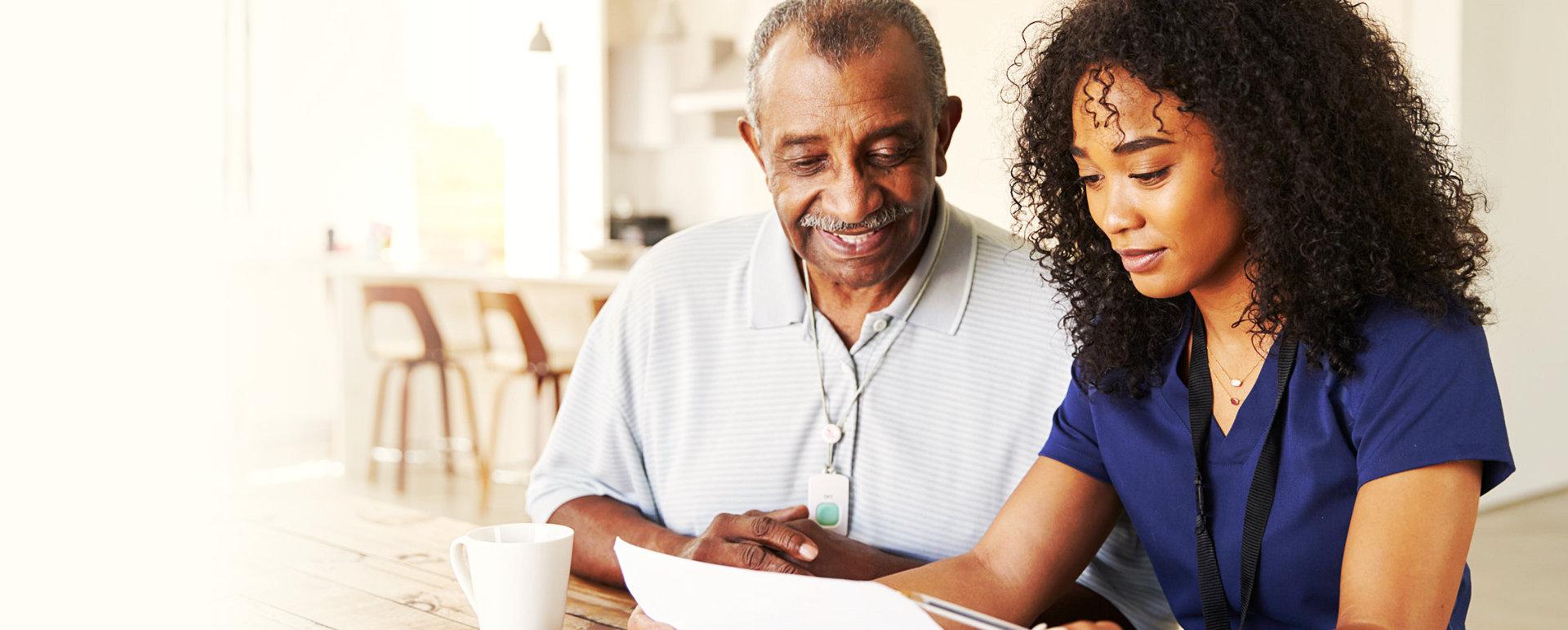 senior man and caregiver looking at paper